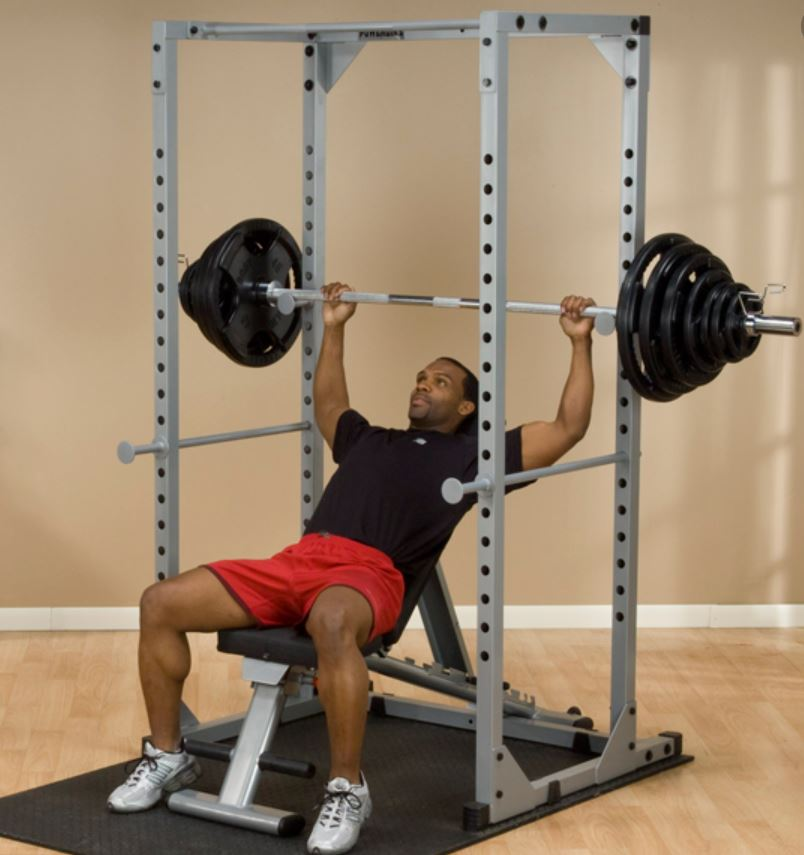 Man doing a military press on power rack