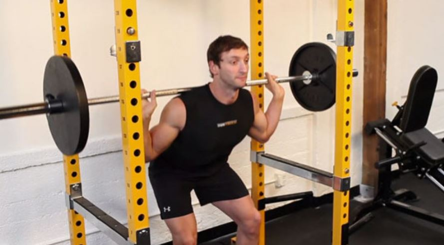 Man doing squats on power rack with weights
