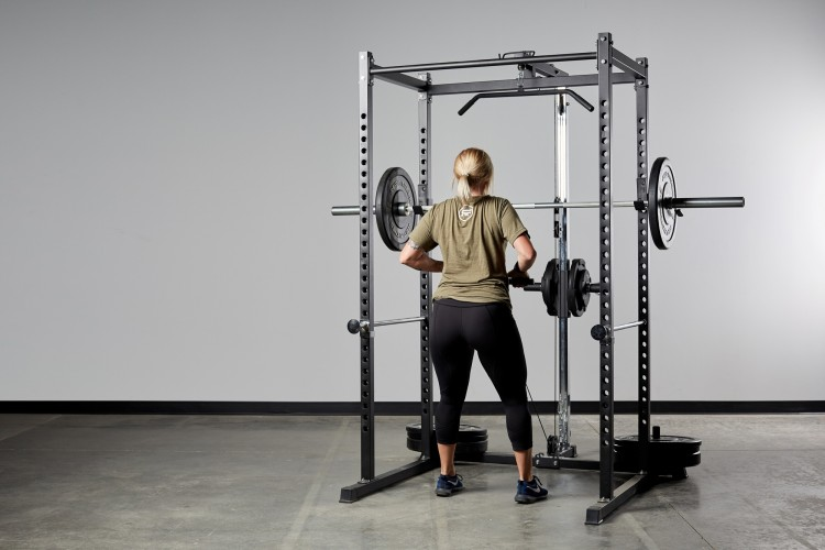 WOman looking at power rack with addons